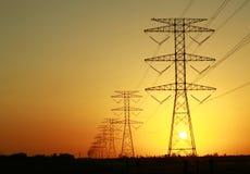 Pilones de la electricidad contra puesta del sol Foto de archivo