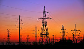 PILONES DE LA ELECTRICIDAD CONTRA PUESTA DEL SOL Fotografía de archivo