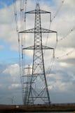 Pilones de la electricidad en campo de la cebada Imagen de archivo