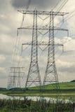 Pilones de la electricidad en fila fotos de archivo