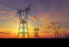 Pilones de la electricidad en la puesta del sol Imagenes de archivo