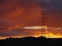 Pilones de la electricidad en la puesta del sol Fotos de archivo