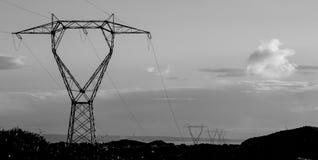 Pilones de la electricidad silueteados contra el cielo Imágenes de archivo libres de regalías