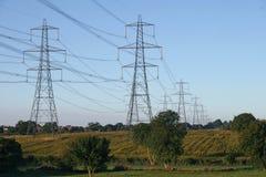 Pilones de la electricidad sobre campo Imágenes de archivo libres de regalías