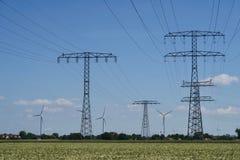 Pilones de la electricidad y turbinas de viento Imágenes de archivo libres de regalías
