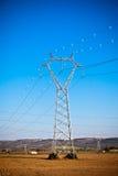 Pilones del poder de la electricidad en un campo hermoso Imagenes de archivo