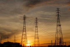 Pilones eléctricos en la salida del sol Imágenes de archivo libres de regalías