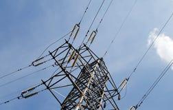 Pilones y línea de la electricidad contra el cielo azul Imagenes de archivo