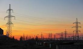 Pilones y líneas eléctricas de la electricidad en la puesta del sol Foto de archivo