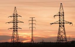 Pilones y líneas de la electricidad en la oscuridad. Imagenes de archivo