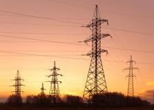 Pilones y líneas de la electricidad en la oscuridad. Imagen de archivo libre de regalías