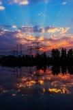 Pilones y líneas de la electricidad en la oscuridad en la puesta del sol Foto de archivo
