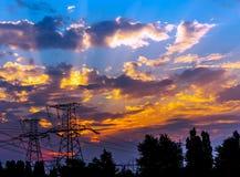 Pilones y líneas de la electricidad en la oscuridad en la puesta del sol Fotografía de archivo