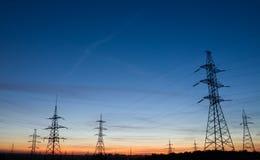 Piloni ad alta tensione di elettricità al bello tramonto Immagine Stock