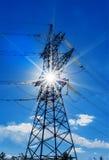 Piloni ad alta tensione di elettricità contro i raggi del sole e del cielo blu Fotografia Stock Libera da Diritti