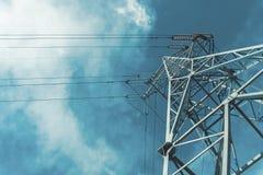 Piloni ad alta tensione di potere contro cielo blu con la nuvola Immagini Stock Libere da Diritti