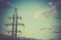 Piloni ad alta tensione di potere contro cielo blu ed il sole Fotografia Stock Libera da Diritti