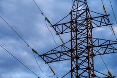 Piloni ad alta tensione di potere contro cielo blu ed il sole Fotografia Stock