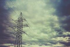 Piloni ad alta tensione di potere contro cielo blu ed il sole Immagini Stock