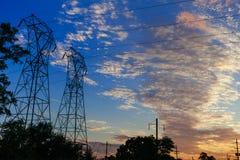 Piloni ad alta tensione di potere nella penombra di scena di tramonto Fotografia Stock