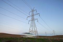 Piloni ad alta tensione sopra una strada provinciale Fotografia Stock