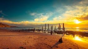 Piloni del molo di Willunga del porto al tramonto Immagine Stock