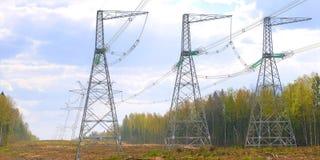 Piloni delle linee elettriche ad alta tensione e un cielo blu con le nuvole fotografia stock libera da diritti