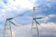 Piloni delle linee elettriche ad alta tensione e un cielo blu con le nuvole fotografia stock