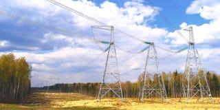 Piloni delle linee elettriche ad alta tensione e un cielo blu con le nuvole fotografie stock