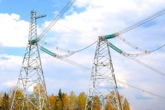 Piloni delle linee elettriche ad alta tensione e un cielo blu con le nuvole immagine stock