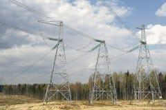 Piloni delle linee elettriche ad alta tensione e un cielo blu con le nuvole immagini stock libere da diritti
