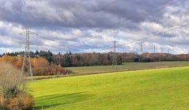 Piloni di Electiricty in un paesaggio inglese Immagini Stock Libere da Diritti