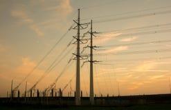 Piloni di elettricità con fondo arancio Immagini Stock Libere da Diritti