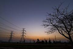 Piloni di elettricità della siluetta Fotografia Stock