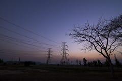 Piloni di elettricità della siluetta Fotografie Stock