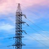 Piloni di elettricità e linee elettriche ad alta tensione della trasmissione sui precedenti del cielo blu Immagine Stock Libera da Diritti