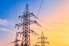 Piloni di elettricità e linee elettriche ad alta tensione della trasmissione sui precedenti del cielo blu Fotografie Stock