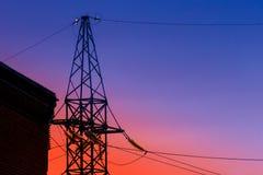 Piloni di elettricità e linee elettriche ad alta tensione della trasmissione sui precedenti del cielo blu Fotografia Stock