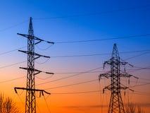 Piloni di elettricità e linee elettriche ad alta tensione della trasmissione sui precedenti del cielo blu Immagini Stock Libere da Diritti