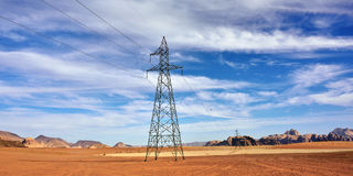 Piloni di elettricità nel campo dell'orzo Immagini Stock Libere da Diritti