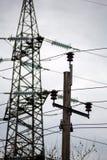 Piloni di elettricità nel campo dell'orzo Fotografie Stock Libere da Diritti