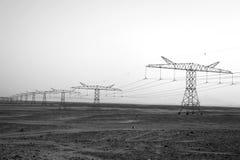 Piloni di elettricità nel deserto della sabbia Fotografie Stock