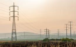 Piloni di elettricità sopra un terreno arabile Immagini Stock
