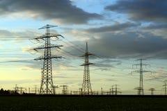Piloni di potere per il trasporto dell'elettricità immagini stock