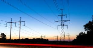 Piloni e linee elettriche di elettricità alla notte con i semafori immagine stock libera da diritti