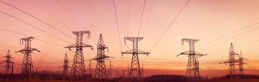 Piloni e righe di elettricità al crepuscolo. Immagine Stock Libera da Diritti