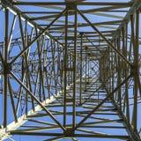 Piloni elettrici che trasportano elettricità con l'alta tensione Ca immagini stock