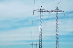 Piloni elettrici contro il cielo Fotografia Stock