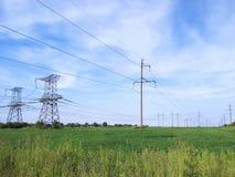Piloni elettrici sul campo verde Immagini Stock Libere da Diritti