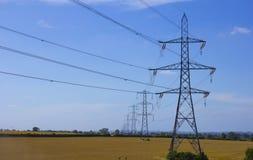 Piloni elettrici in un campo Fotografia Stock